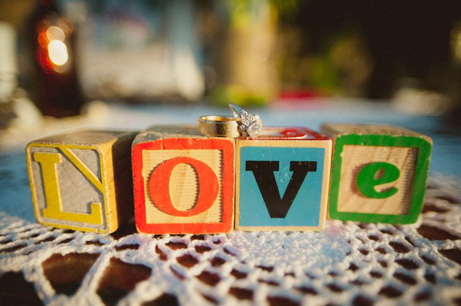 wedding rings on vintage mismatched alphabet blocks spelling love