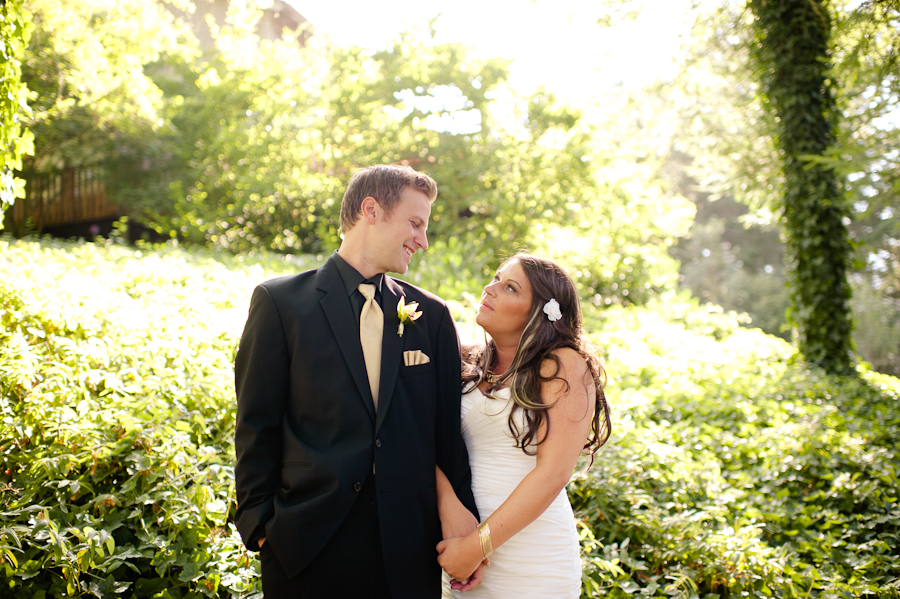 Groom in black suit with gold tie and bride stand under trees.