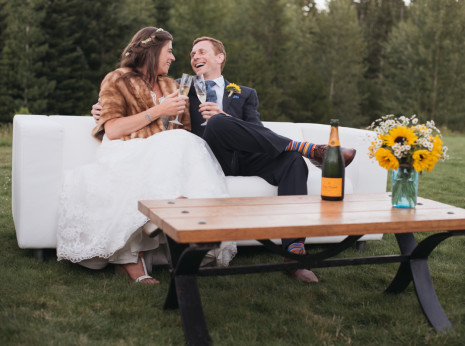 couple toasting champagne on white couch.